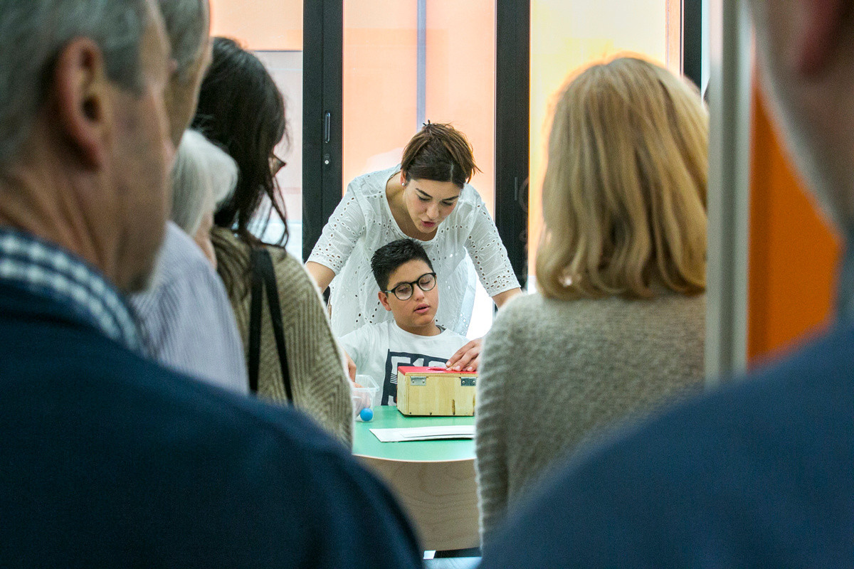Domenico svolge attività riabilitative con la sua educatrice mentre i sostenitori in visita osservano