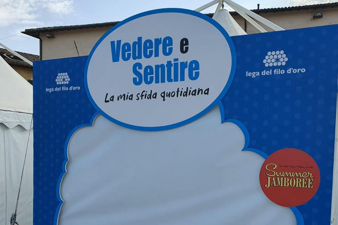 """Lo stand della Lega del FIlo d'Oro al Summer Jamboree, blu con le scritte bianche. Sulla facciata c'è la scritta """"Vedere e sentire la mia sfida quotidiana""""."""