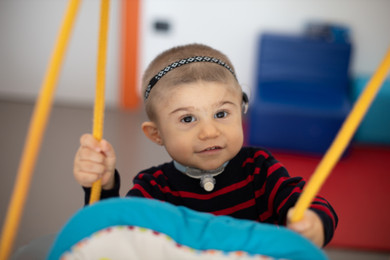 Berk, piccolo utente del Centro di Osimo, guarda verso l'obiettivo con un sorriso, mentre dondola su un'altalena in una delle aule del Centro Nazionale