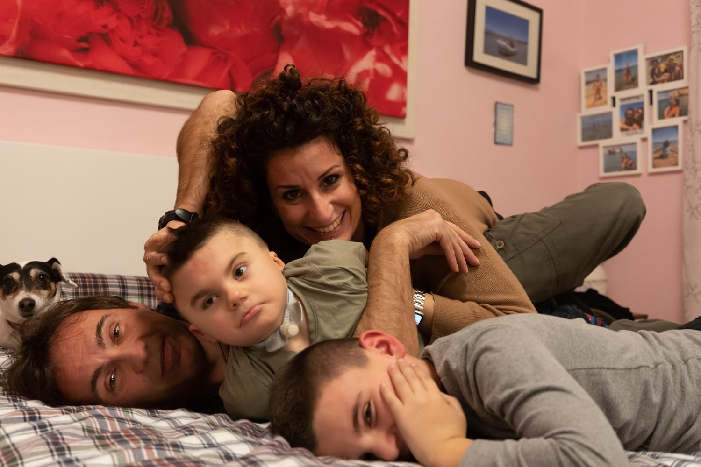 Foto della famiglia di Leonardo, un bvambino affetto dalla sindrome di Charge, seguito dalla lega del filo d'Oro. Ci sono la mamma, il papà, Leonardo e il fratello maggiori e la loro piccola cagnolina. Sono stesi sul letto, sorridono alla camera