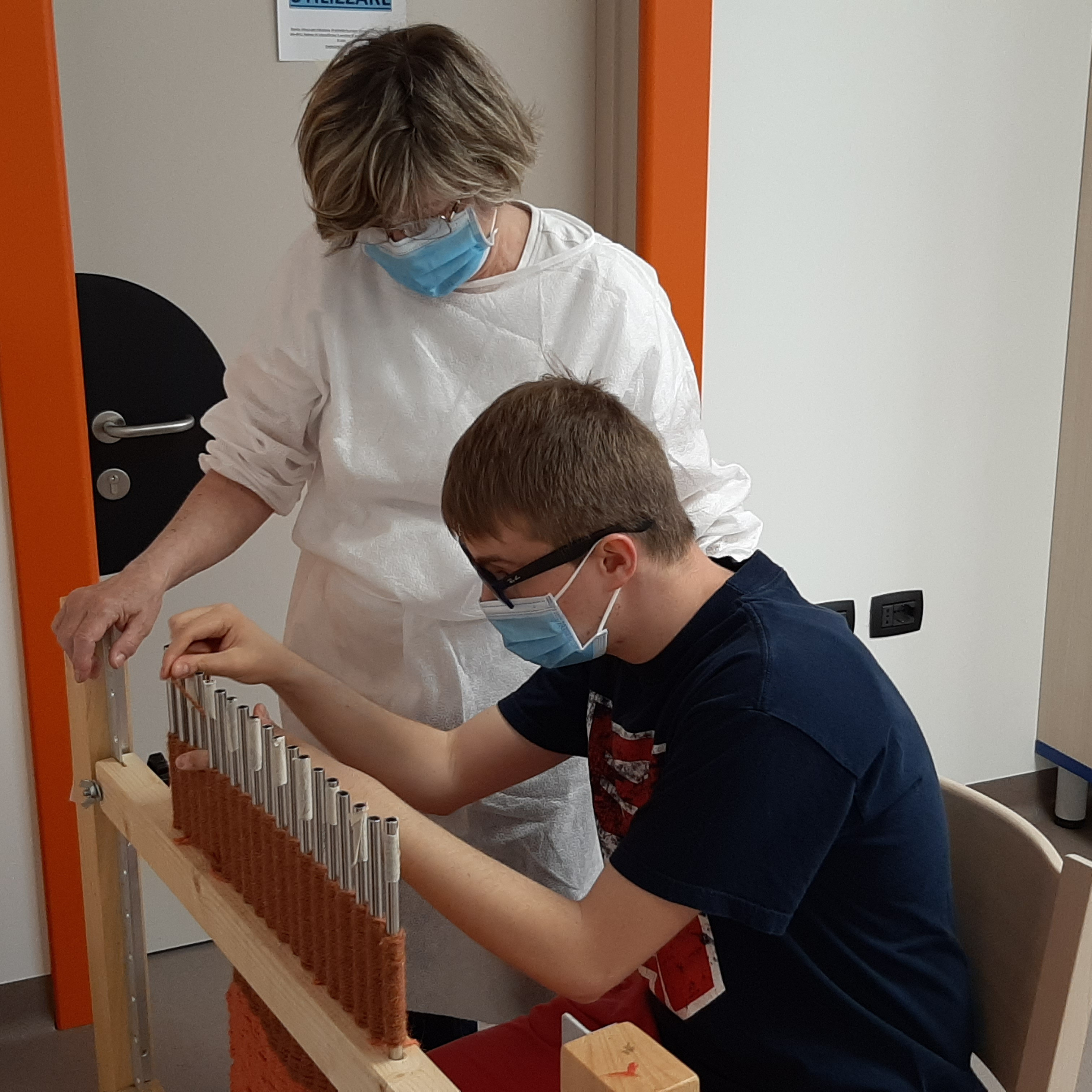Un utente e un'educatrice nel laboratorio di filato con DPI anti covid