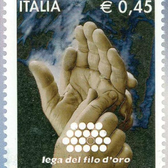 Un francobollo con l'immagine di due mani che comunicano con il Metodo Malossi. In alto a sinitra c'è la scritta Italia, in alto a destra è indicato il prezzo € 0,45, in basso c'è il logo della Lega del Filo d'Oro, con scritta e pallini bianchi.