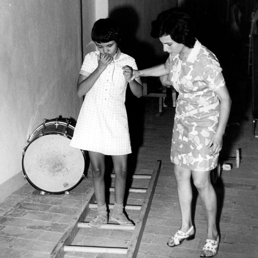 Una bambina sordocieca viene aiutata da un'operatrice in un esercizio. C'è una scala appoggiata a terra e lei deve camminare senza toccare i pioli. Foto degli anni '70 e in bianco e nero.