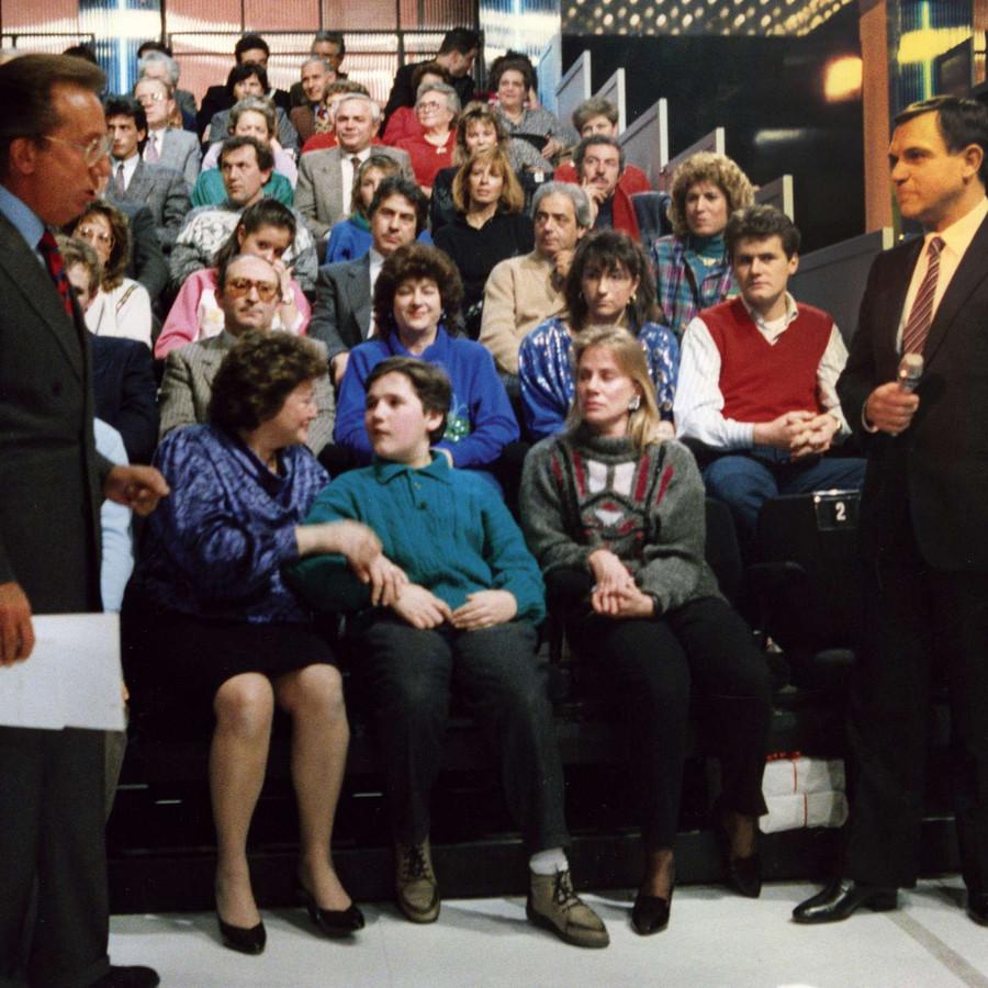 Alcuni utenti sordociechi sono nello studio della trasmissione Penthatlon di Mike Bongiorno. Davanti a loro il presidentatore, in piedi, ascolta un altro uomo, anche lui in piedi e col microfono in mano.