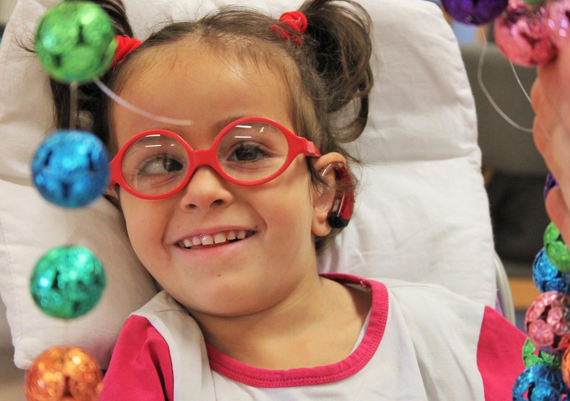La piccola sofia sorride mentre con l'educatrice svolge un'attività di stimolazione sensoriale: toccare un telaio con appesi tanti sonagli colorati