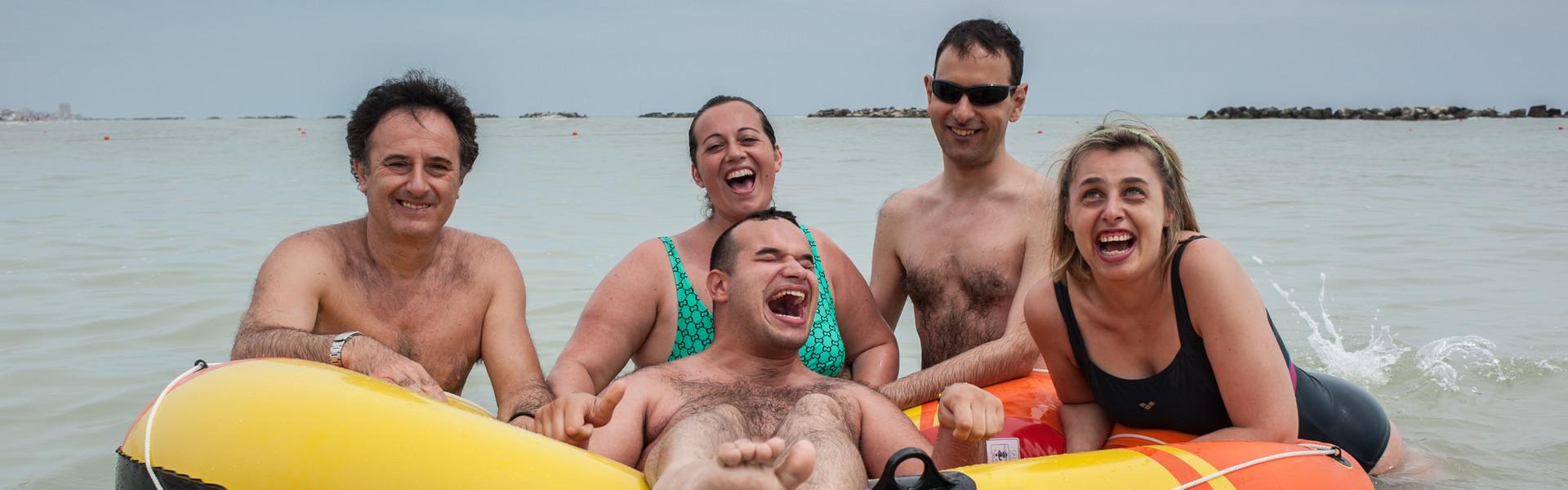 Soggiotni estivi al mare: un utente ride di gusto galleggiando su un gommone mentre volontari ed altri utenti, appoggiati intorno al gommone, ridono insieme a lui